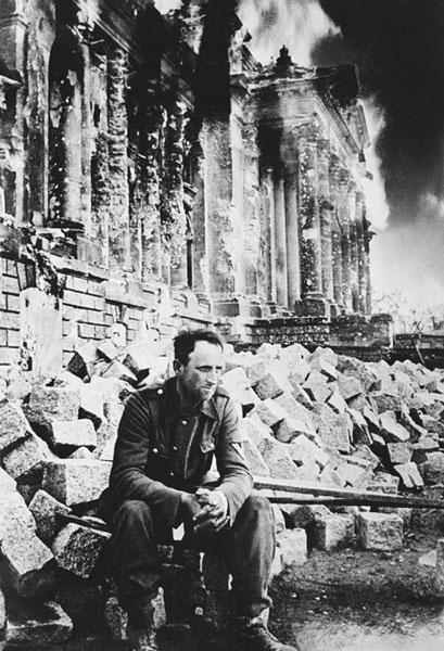 Пленный немецкий солдат на фоне горящего рейхстага.
